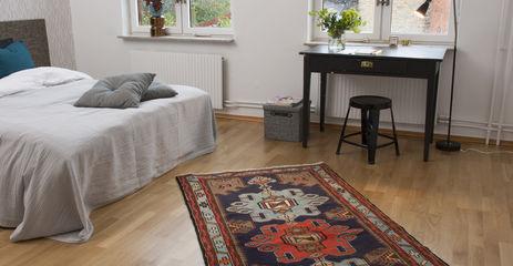 ベッドルーム内の黒色の / グレーのてハマダン絨毯。